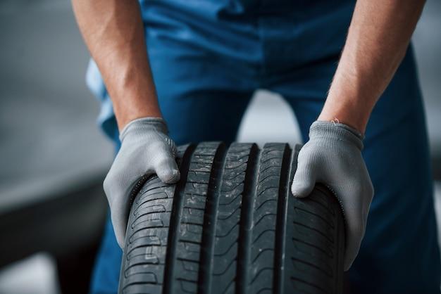 Sujeira na roda. mecânico segurando um pneu na oficina. substituição de pneus de inverno e verão Foto gratuita