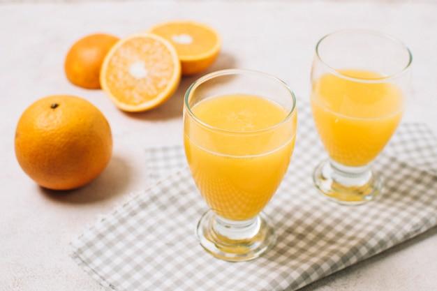 Sumo de laranja fresco de alto ângulo em vidro Foto gratuita