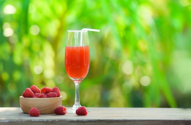 Sumo de vidro suco de verão coquetel e framboesas frescas frutas na tigela de madeira Foto Premium