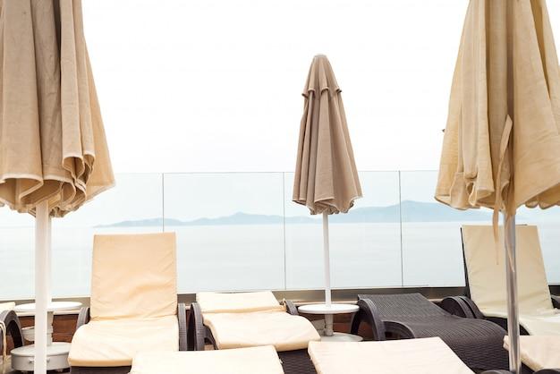 Sun guarda-chuvas cor bege e espreguiçadeiras perto da piscina com vista para o mar. Foto Premium
