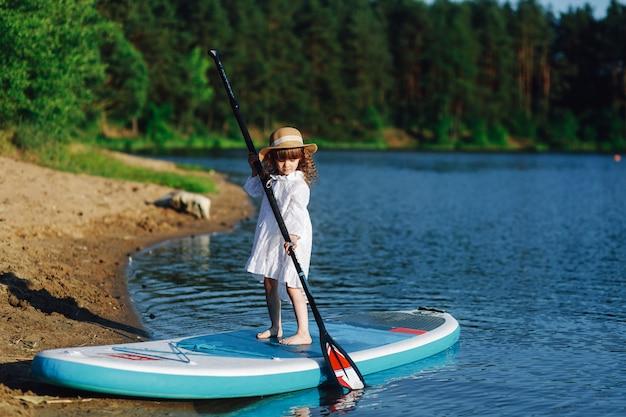 Sup a garota em um vestido branco com uma prancha flutua na água. Foto Premium