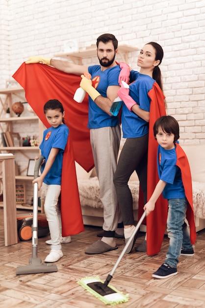Super-herói feliz família limpeza casa com crianças. Foto Premium