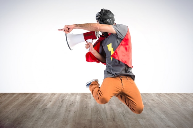 Super-herói gritando por megafone em fundo colorido Foto Premium