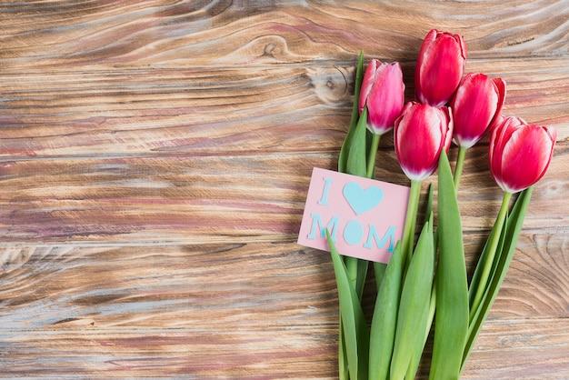 Superfície de madeira com belas flores e cartão para o dia da mãe Foto gratuita