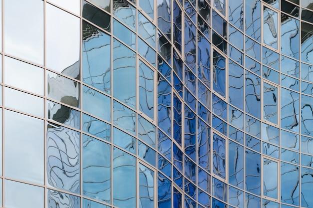 Superfície de vidro do espelho do arranha-céus que reflete o céu nebuloso, superfície curvilínea Foto Premium