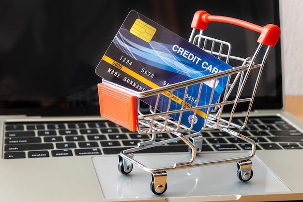 Supermercado de cartão e carrinho de crédito na mesa de madeira. conceito de compras Foto Premium