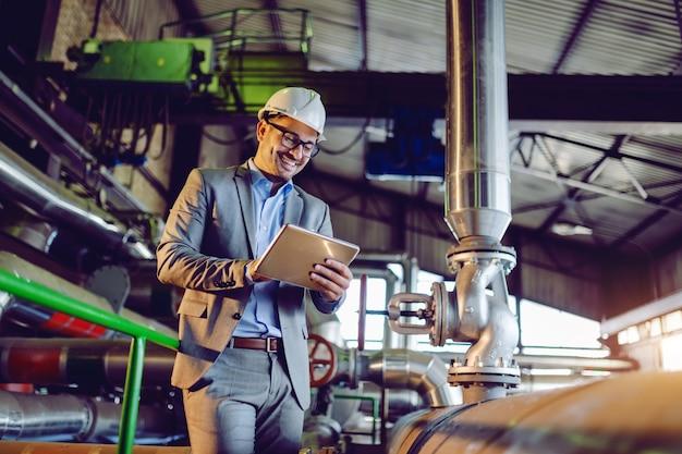 Supervisor caucasiano de sorriso considerável no terno e com o capacete na cabeça usando a tabuleta ao estar na usina. Foto Premium
