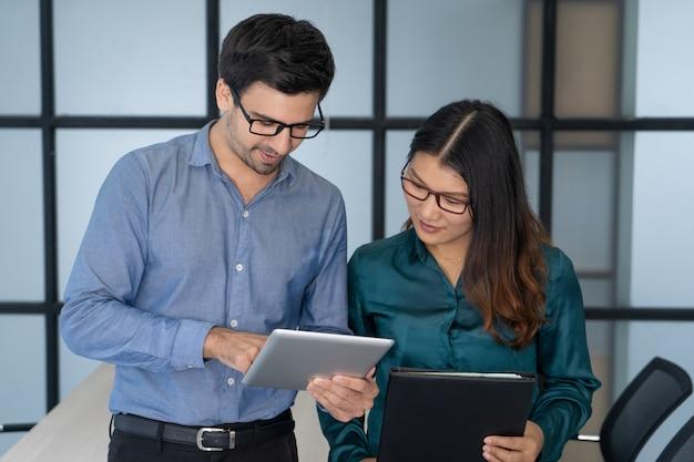 Supervisor caucasiano que ajuda o empregado asiático novo. Foto gratuita