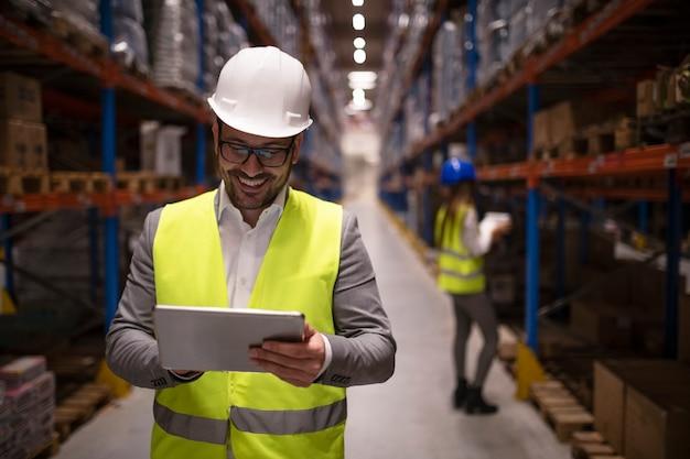 Supervisor de armazém lendo relatório em tablet sobre entrega e distribuição bem-sucedidas no centro de logística do armazém Foto gratuita