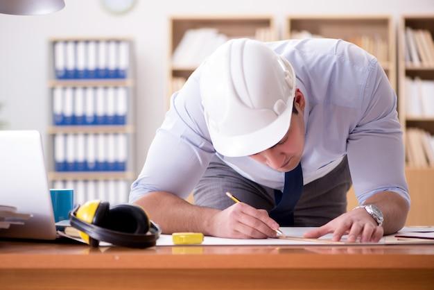 Supervisor de engenheiro trabalhando em desenhos no escritório Foto Premium