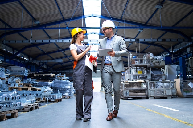 Supervisor gerente e trabalhador industrial uniformizado caminhando no grande salão de uma fábrica de metal e falando sobre o aumento da produção Foto gratuita