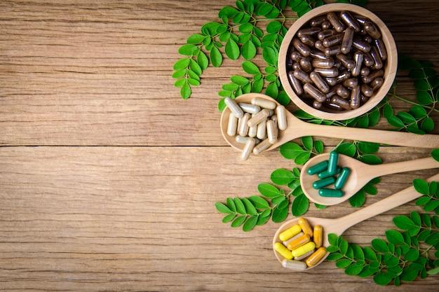 Suplemento de ervas medicinais de natural no fundo da mesa de madeira e espaço de cópia Foto Premium