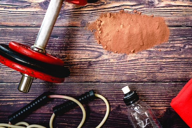 Suplemento de soro de proteína de cacau em pó no chão de uma academia durante um treino. Foto Premium