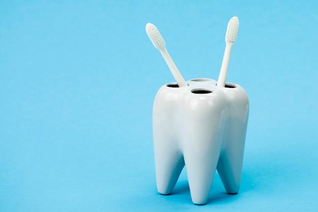 Suporte de escova de dentes em forma de dente duas escovas de dentes isoladas na parede azul Foto Premium