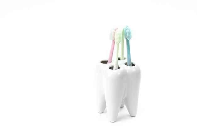 Suporte de escova de dentes em forma de dente primário com escovas de dentes coloridas Foto Premium