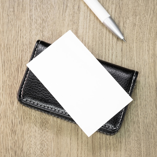 Suportes de cartão de couro preto no fundo de madeira. Foto Premium