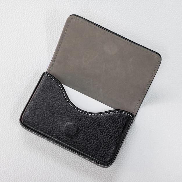 Suportes de cartão de couro pretos e cartão branco no fundo branco sintético. Foto Premium