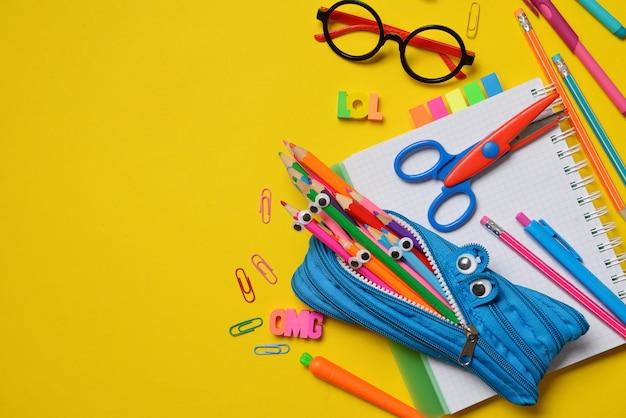 Suprimentos coloridos de escritório e estudante em amarelo Foto Premium