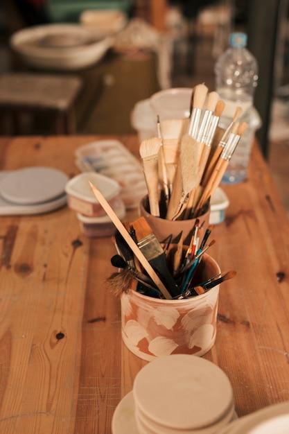 Suprimentos com pincéis e ferramentas em suporte de barro artesanal na mesa de madeira Foto gratuita