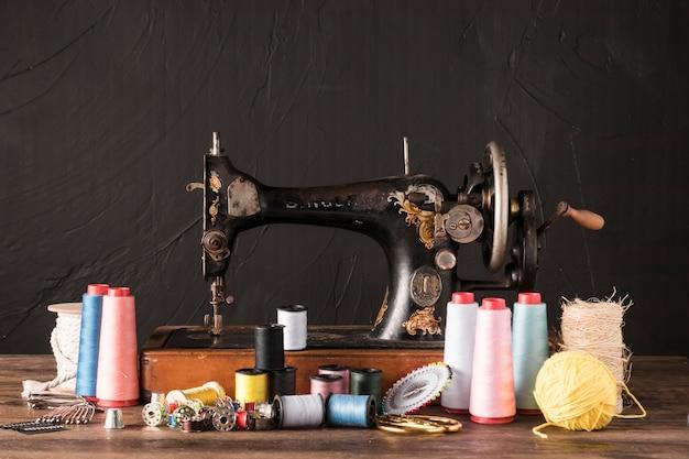 Suprimentos de costura perto da máquina retro Foto gratuita
