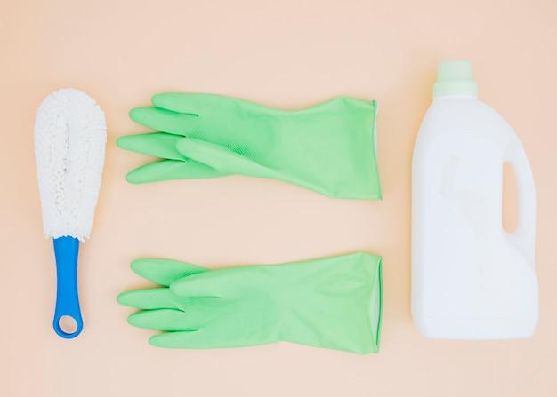 Suprimentos de limpeza como escova; luvas verdes e detergente podem no pano de fundo pêssego Foto gratuita