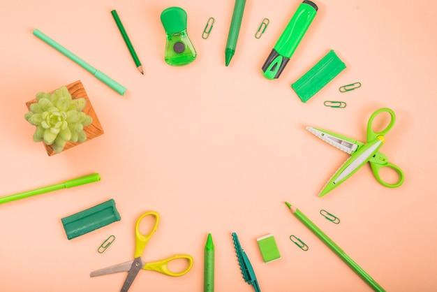Suprimentos de papelaria e planta em vaso, formando uma moldura circular sobre a superfície colorida Foto gratuita