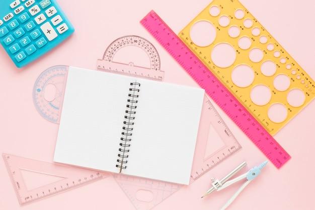 Suprimentos de réguas matemáticas com caderno vazio aberto plano leigos Foto gratuita