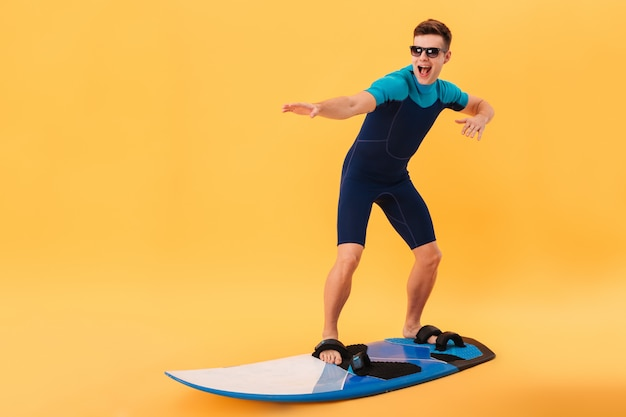 Surfista feliz em roupa de mergulho e óculos de sol usando prancha como na onda Foto gratuita