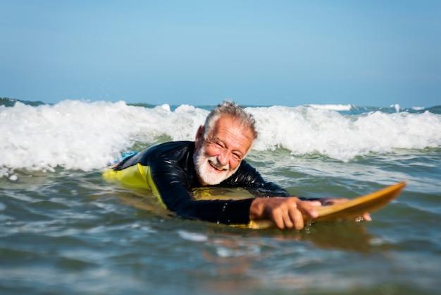 Surfista maduro pronto para pegar uma onda Foto gratuita