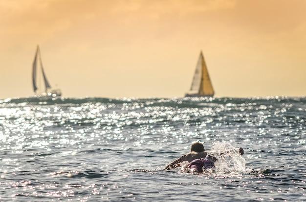 Surfista masculina remando ao pôr do sol no havaí com veleiros no fundo Foto Premium