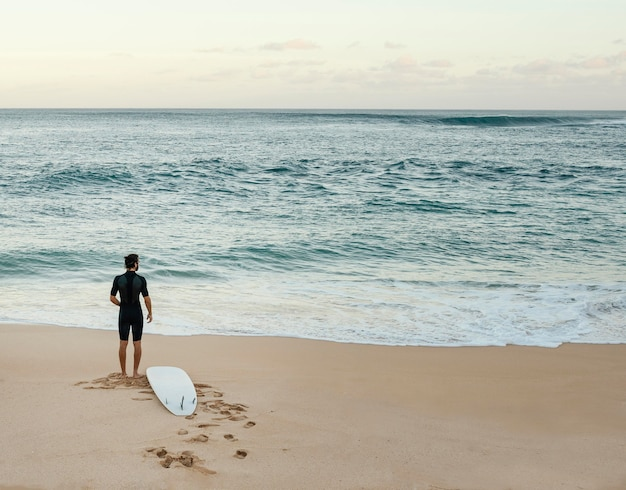 Surfista olhando para o mar em tiro plano horizontal Foto gratuita