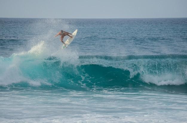 Surfista, pular, um, onda, em, ponto rochoso, ligado, a, costa norte, de, oahu, havaí, eua Foto Premium