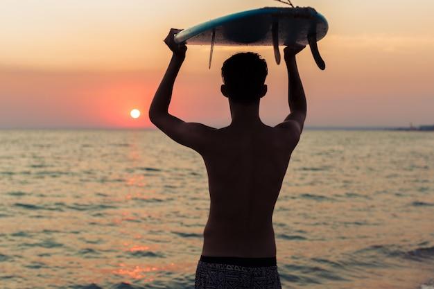 Surfista segurando sua prancha de surf e procurando ondas Foto Premium