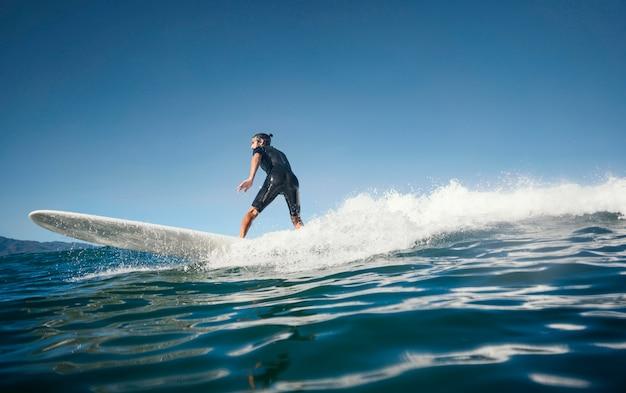 Surfista surfando na onda à luz do dia Foto gratuita