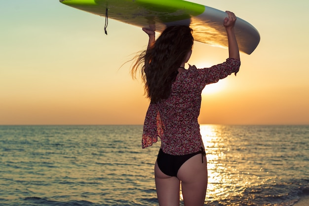 Surfista surfando olhando para o pôr do sol praia do oceano Foto Premium