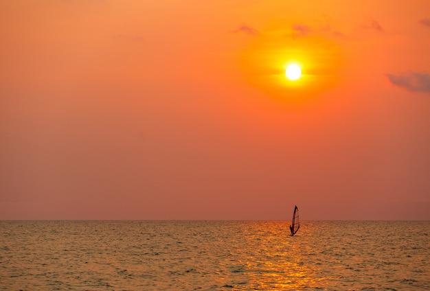 Surfista surfando sozinho no mar ao pôr do sol Foto Premium