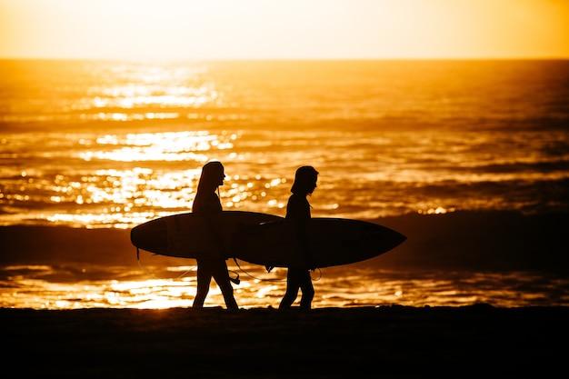 Surfistas caminhando após uma sessão exaustiva de surfe em um cenário deslumbrante do pôr do sol Foto gratuita
