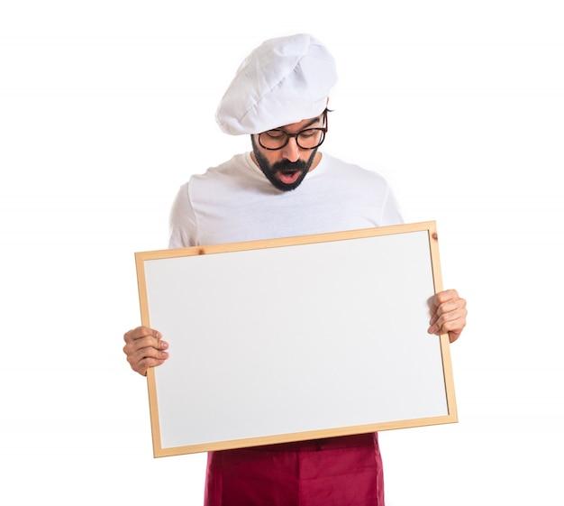 Surpreendido, cozinheiro, segurando, vazio, placard Foto gratuita