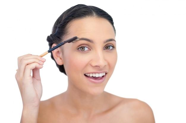 Surpreendido, jovem, morena, usando, sobrancelha, escova Foto Premium