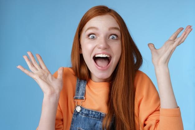 Surpresa espantada sensível oprimida jovem feliz ruiva recebe incrível prêmio fantástico olhos arregalados espantado levantando as mãos triunfando ganhar loteria comemorando com alegria. Foto gratuita