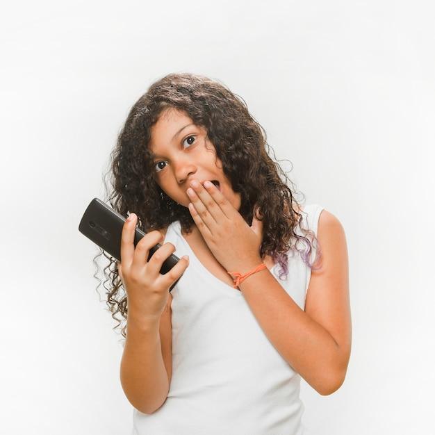 Surpresa garota segurando o telefone móvel Foto gratuita