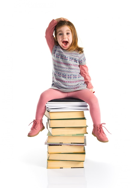 Surpresa garotinha sentado nos livros. de volta à escola Foto Premium