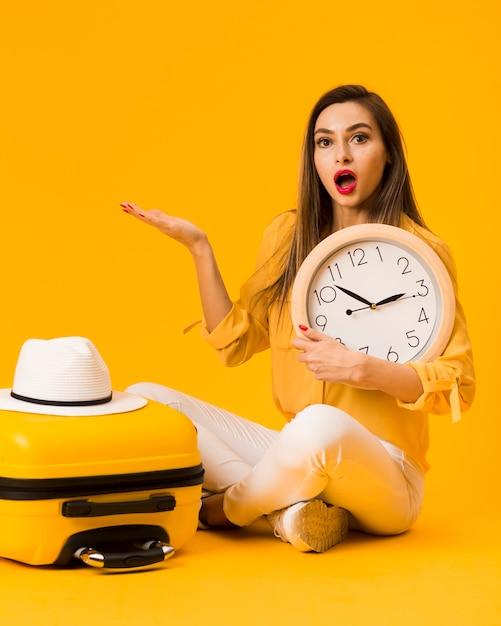 Surpresa mulher segurando o relógio ao lado de bagagem com chapéu em cima Foto gratuita
