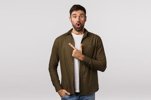 Surpreso e espantado, jovem homem barbudo, sem casaco, lábios dobrados, ofegando, impressionado, apontando o canto superior esquerdo espantado, ouviu um evento interessante ocorrendo nas proximidades, discutir notícias Foto Premium