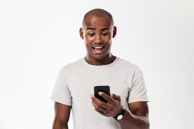 Surpreso homem africano usando smartphone Foto gratuita