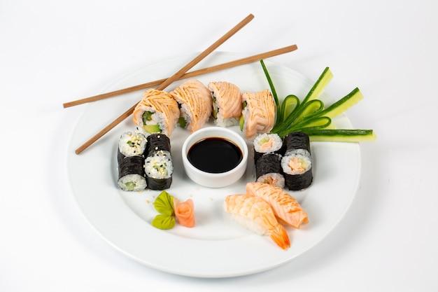 Sushi com molho de soja no meio de um prato e pauzinhos Foto gratuita
