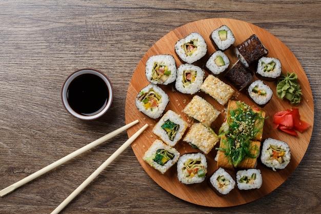 Sushi conjunto na placa de madeira redonda Foto Premium