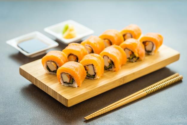 Sushi de carne de peixe salmão roll maki na placa de madeira Foto gratuita