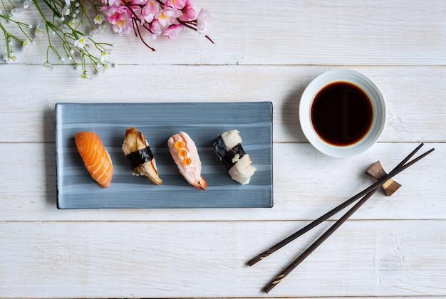 Sushi de sashimi com molho de soja na mesa de madeira branca, vista superior Foto Premium