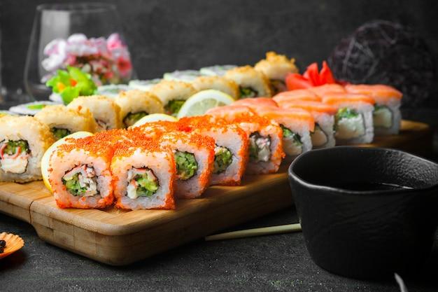 Sushi de vista lateral com molho de soja e pauzinhos na tábua de madeira Foto gratuita